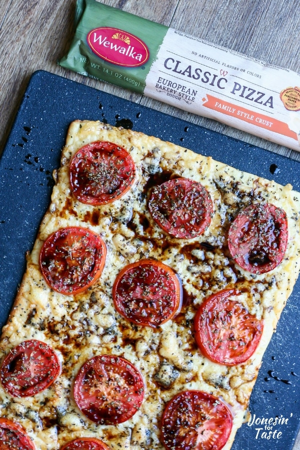 Cooked tomato pizza on a black cutting board