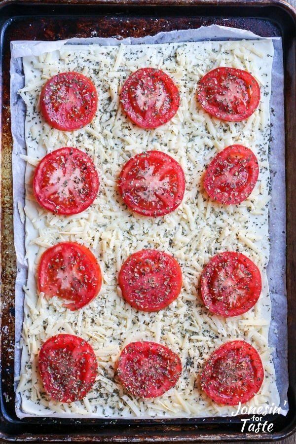 An uncooked tomato pizza on a cookie sheet