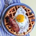 Cornmeal waffle topped with polska kielbasa and fried egg on a blue plate