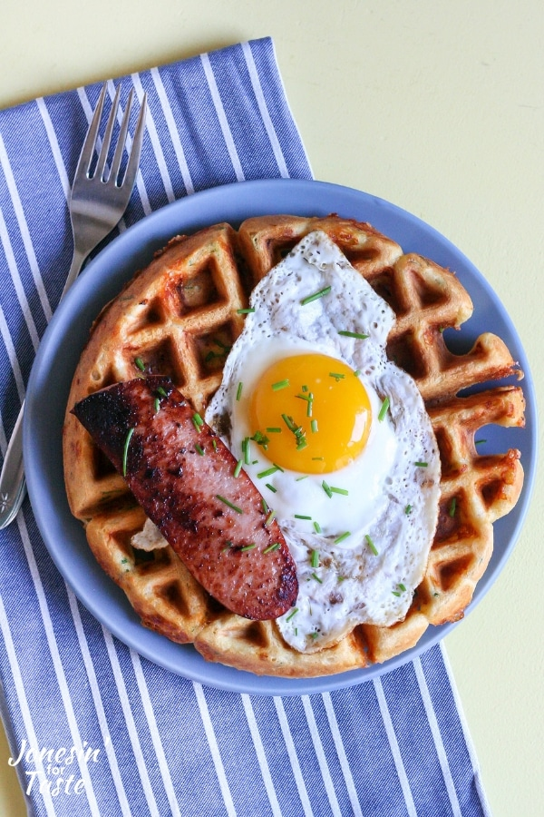Cornmeal waffle topped with polska kielbasa and fried egg on a blue plate