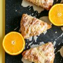 Scones on a cutting board next to halved oranges