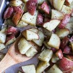 a wooden spoon on a cookie sheet of roasted potatoes