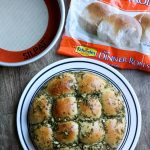 A plate with pesto rolls next to a pan and bag of frozen rolls