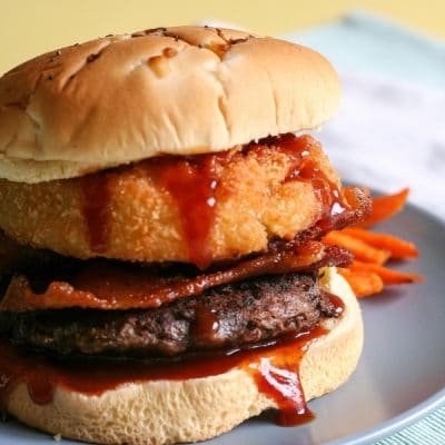 A burger with bbq sauce, bacon, and onion ring