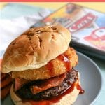 A cowboy burger on a plate next to the Cars DVD box