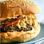 A burger with siracha mayo, a burger patty topped with Korean coleslaw