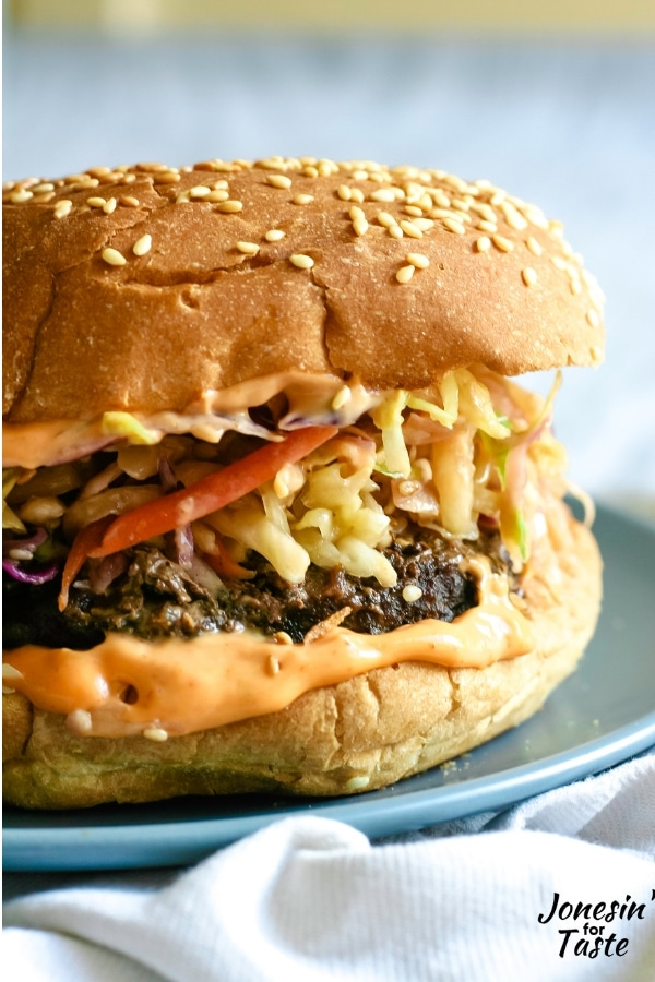 A korean bbq burger with siracha mayo, a burger patty topped with Korean coleslaw