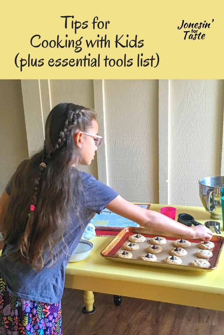A girl adding decorations to cooked cookies