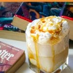 a butterbeer ice cream float next to harry potter books