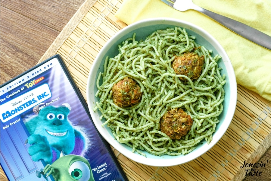 a bowl of pasta next to a monsters inc DVD
