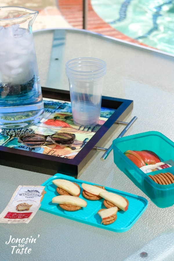 a table with a snack container and water next to a pool