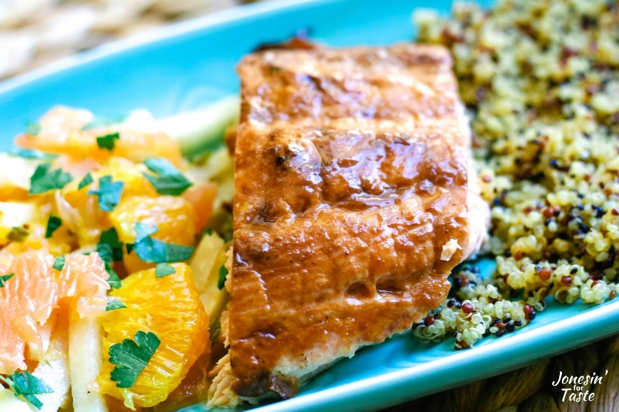 orange bbq salmon on a blue plate with citrus salad and quinoa