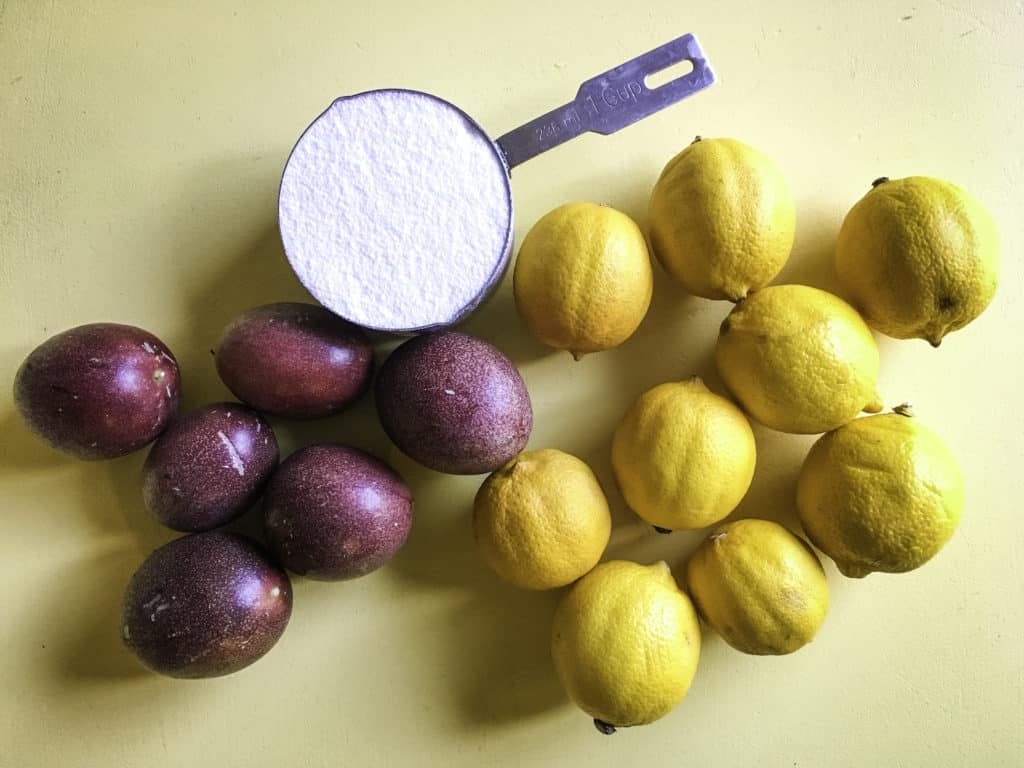 passion fruits, lemons, and a cup of sugar on a yellow table