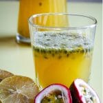a glass of lemonade with halved lemons and passion fruit in front of it