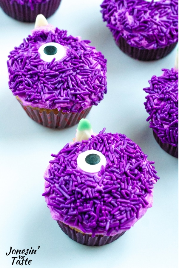 cupcakes covered with purple sprinkles and giant candy eyes