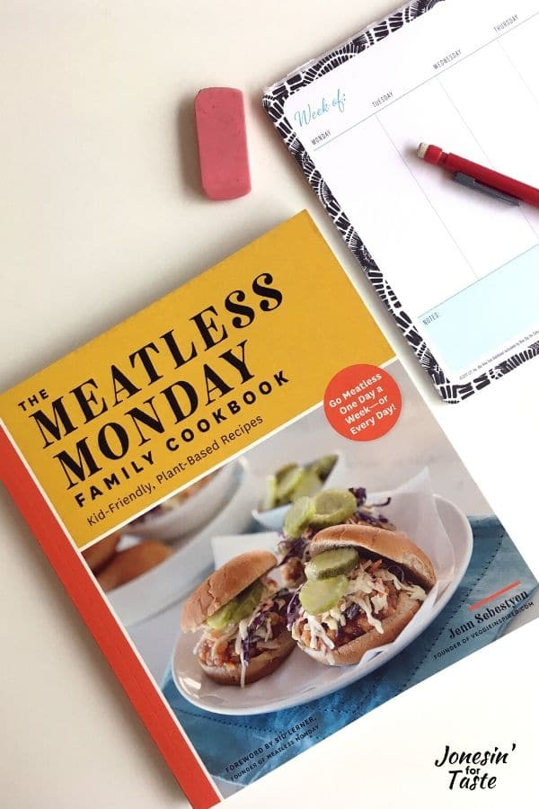 the meatless monday cookbook next to a meal planner