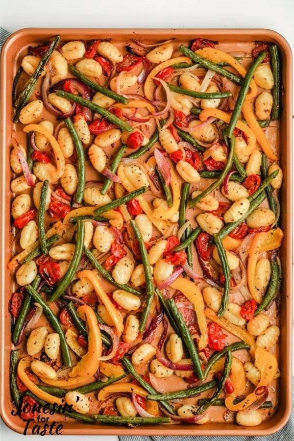 a cookie sheet with cooked gnocchi and veggies