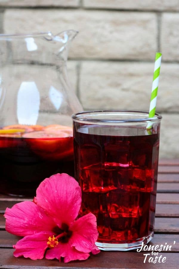 a glass of juice next to a pitcher and a hibiscus flower
