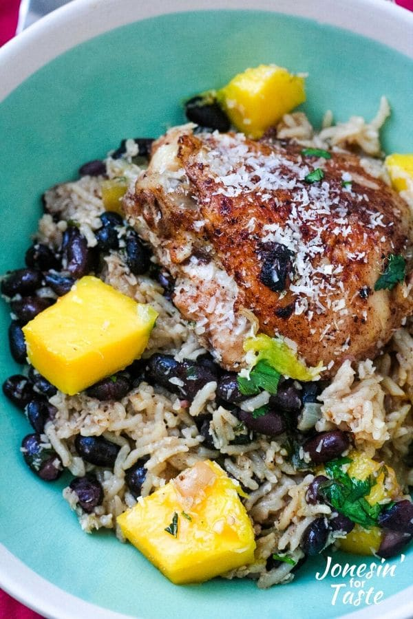 a bowl of coconut rice, black beans, and chicken topped with diced mangoes