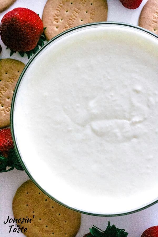 a bowl of coconut fruit dip surrounded by strawberries and crackers