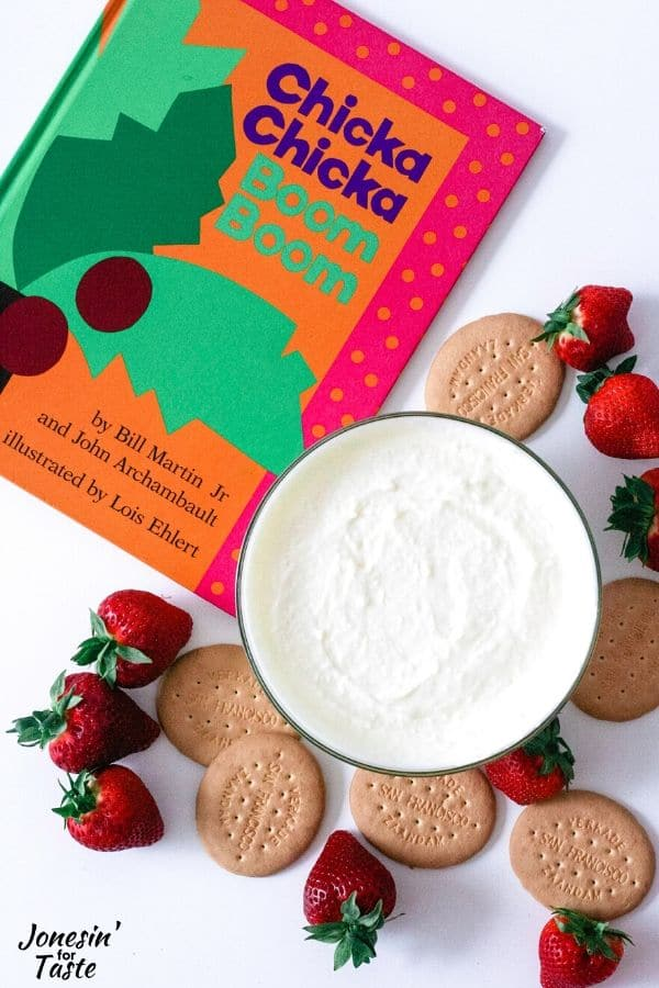 a bowl of coconut dip next to a book, strawberries, and crackers