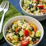 two bowls of couscous salad next to a green napkin with 2 forks