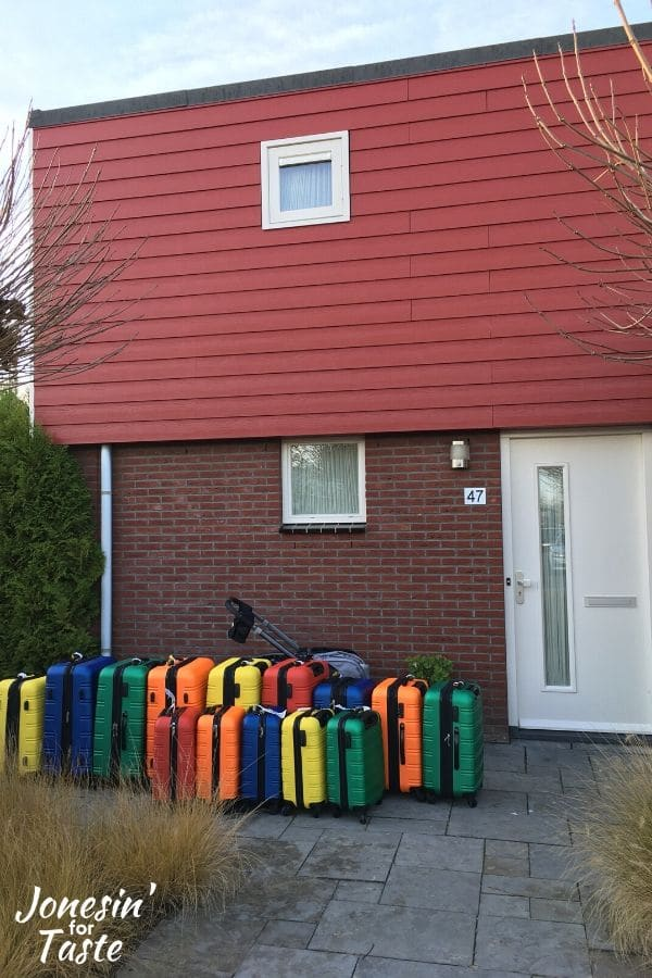 colorful suitcases outside of a house