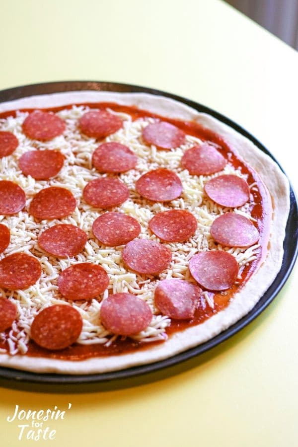an uncooked pepperoni pizza