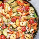 a large pan filled with tortellini and a rainbow of vegetables