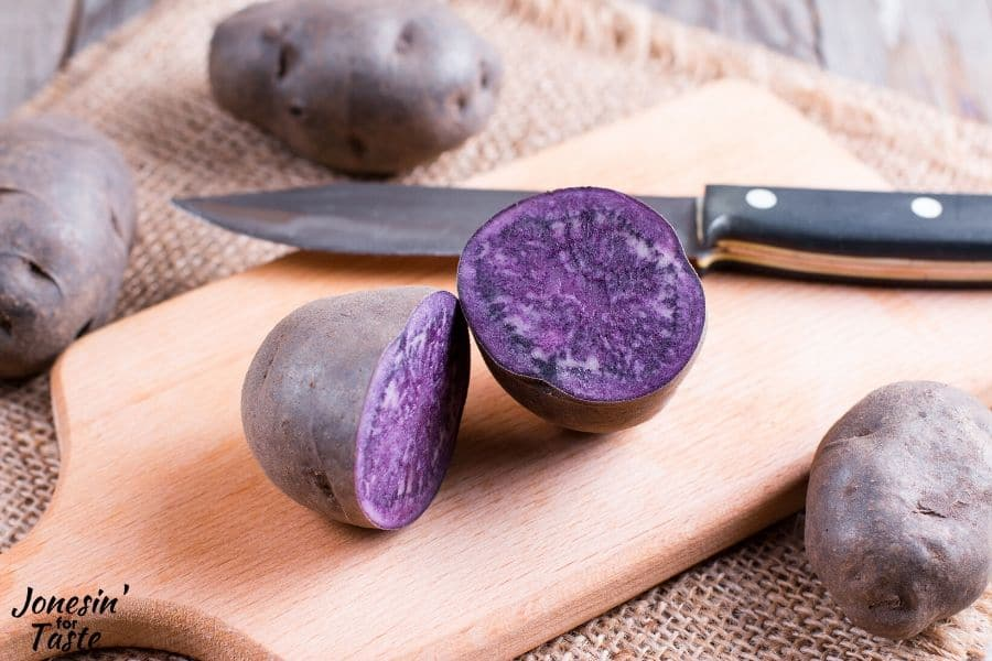 a purple potato cut in half on a cutting board