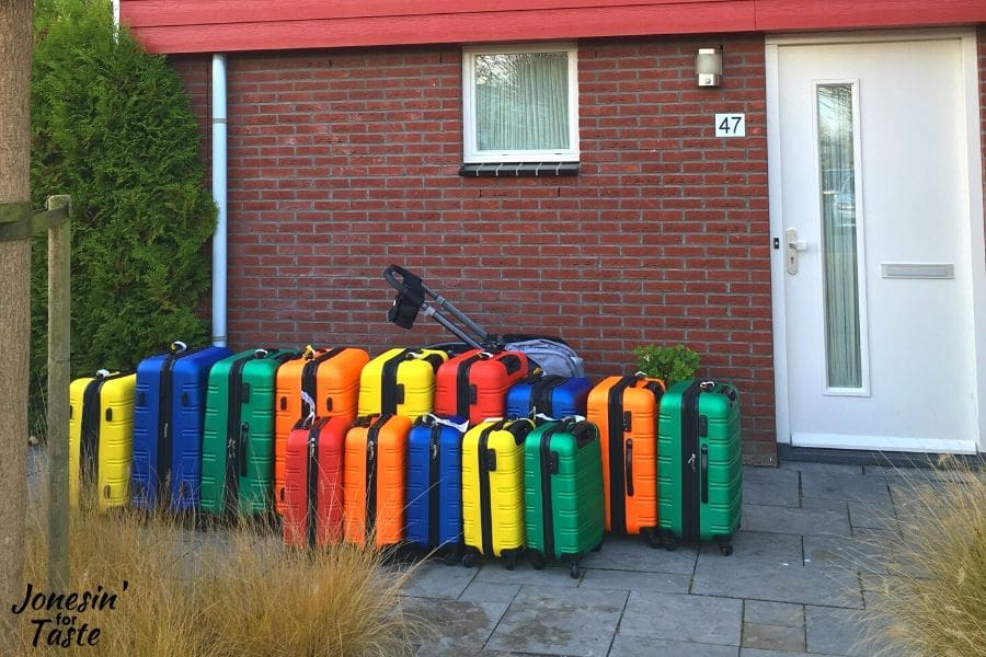 colorful suitcases lined up outside a house