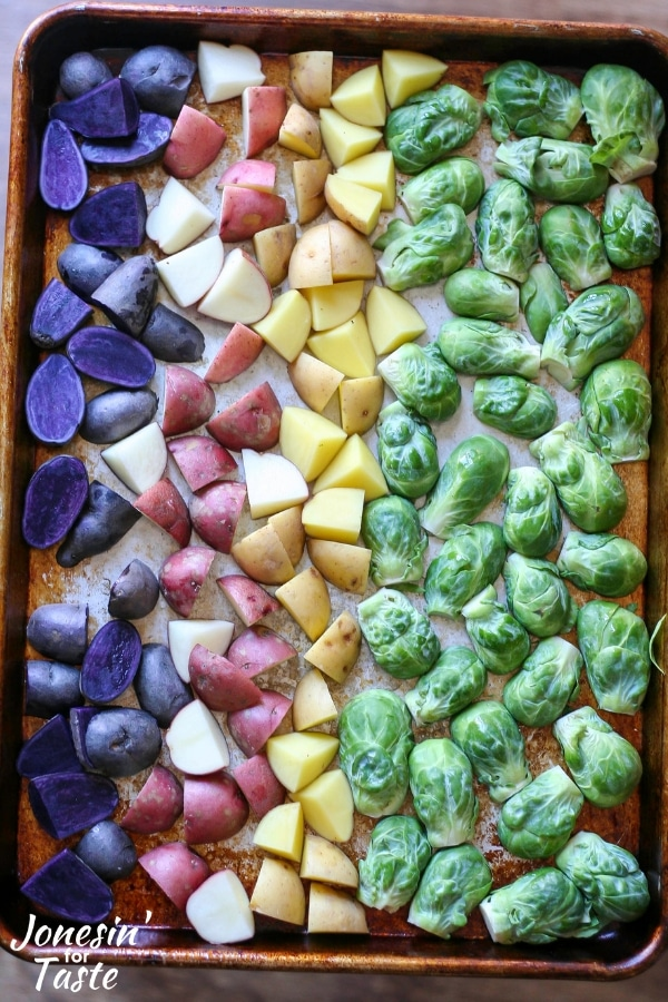 purple, red, and yellow potatoes in rows next to a row of green brussel sprouts