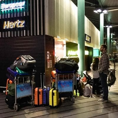 luggage trolleys loaded with baggage outside a car rental counter