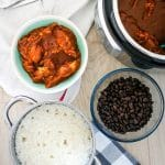 bowls of rice, beans, and mole chicken