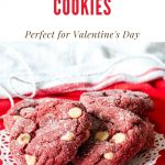 red velvet cookies on a doily on top of red fabric with a text graphic above it with the name of the recipe