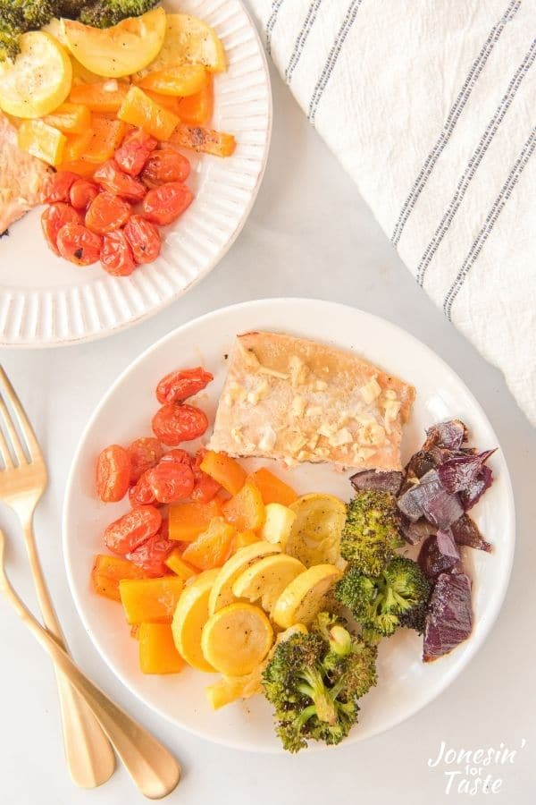 a piece of salmon and veggies on a white plate