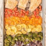 honey mustard salmon fillets with rows of veggies arrange in a rainbow pattern on a sheet pan