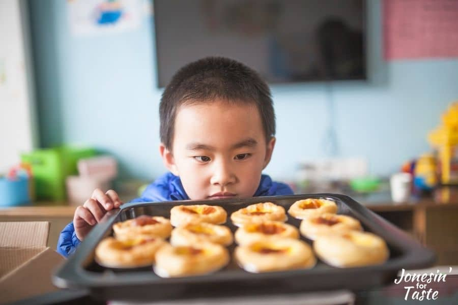 a child looking at a pan filled with pastries