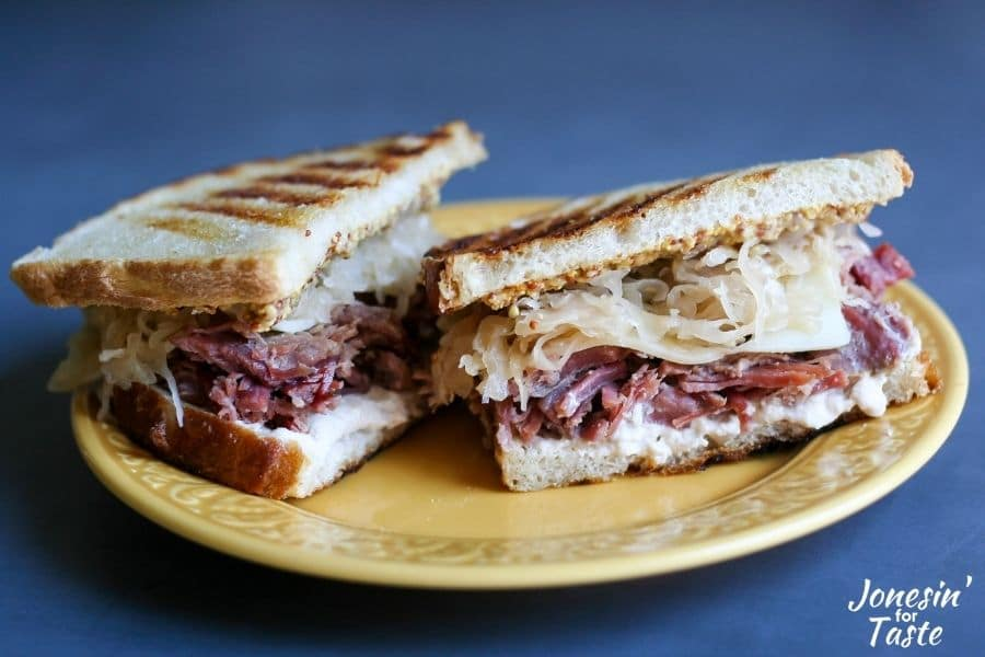 a corned beef and sauerkraut sandwich halved and sitting on a yellow plate