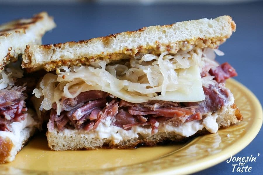 layers of sauerkraut, swiss cheese, and corned beef between slices of grilled sourdough bread