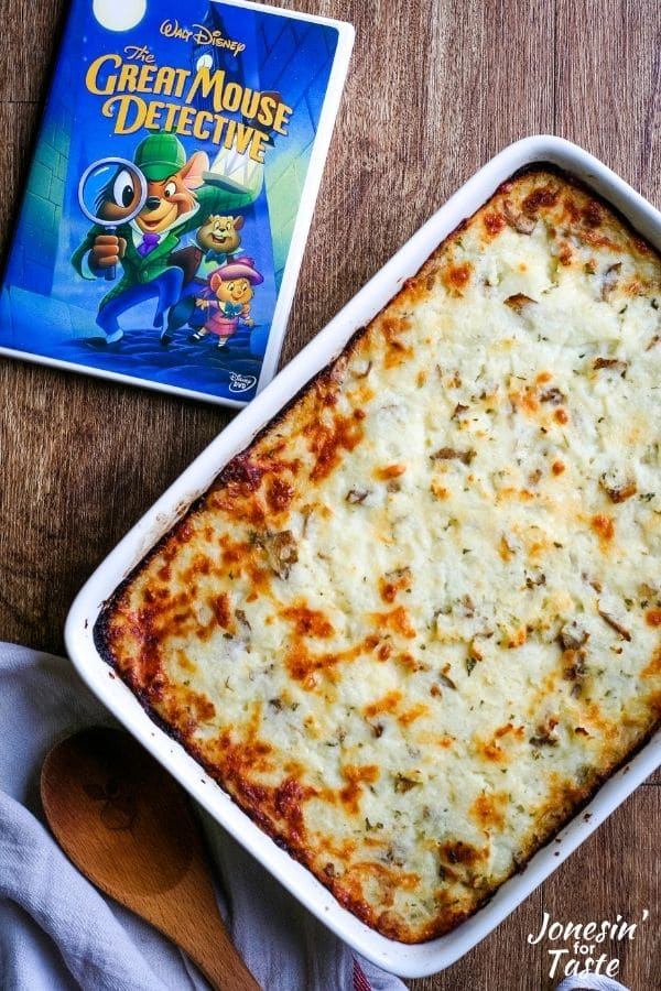 a casserole dish of cottage pie with a golden speckled crust lays next to a DVD case