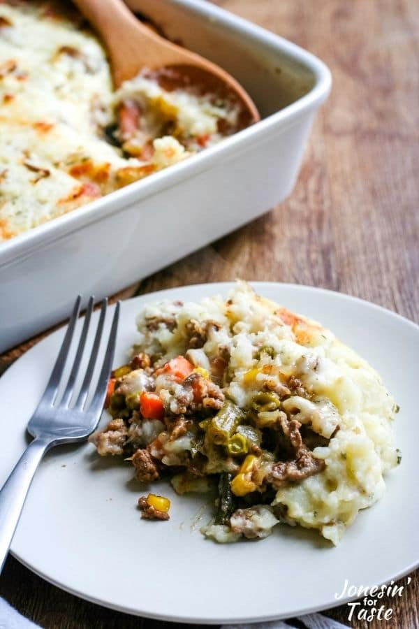saucy ground beef mingled with corn, carrots, and green beans topped with mashed potato on a plate
