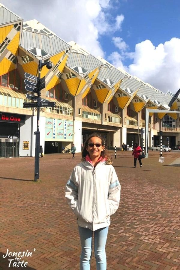 a girl in a white jacket stands in front of the row of Rotterdam's cube houses