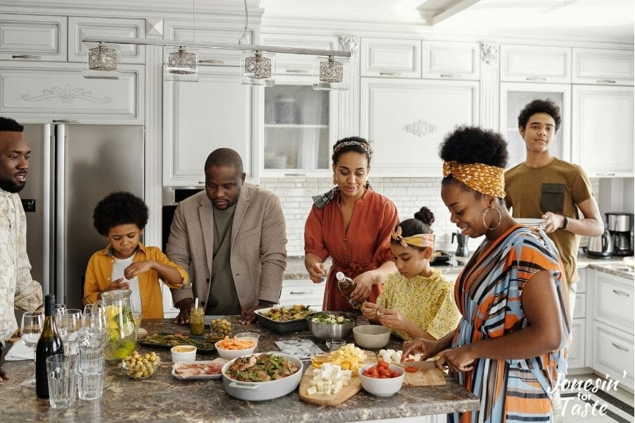 aa family gathering around a kitchen island dishing up various foods for themselves and others