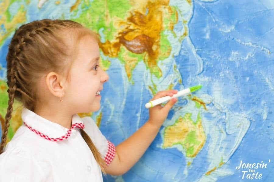 a little girl using a pen to point to a place on a world map