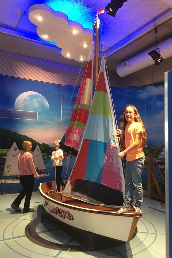 children play on a small sailboat display while a mother looks on