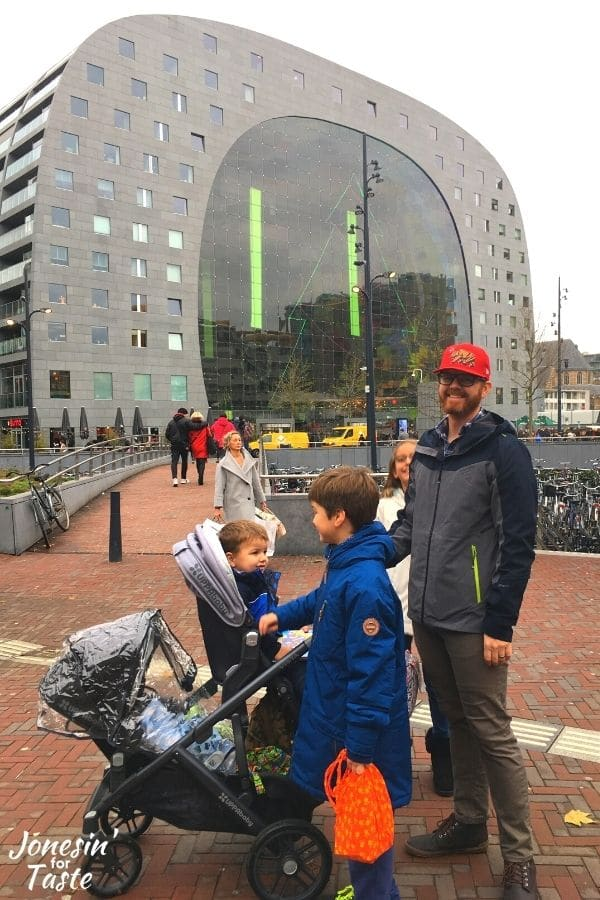a man stands with his children and a stroller in front of the famous Markthal in Rotterdam