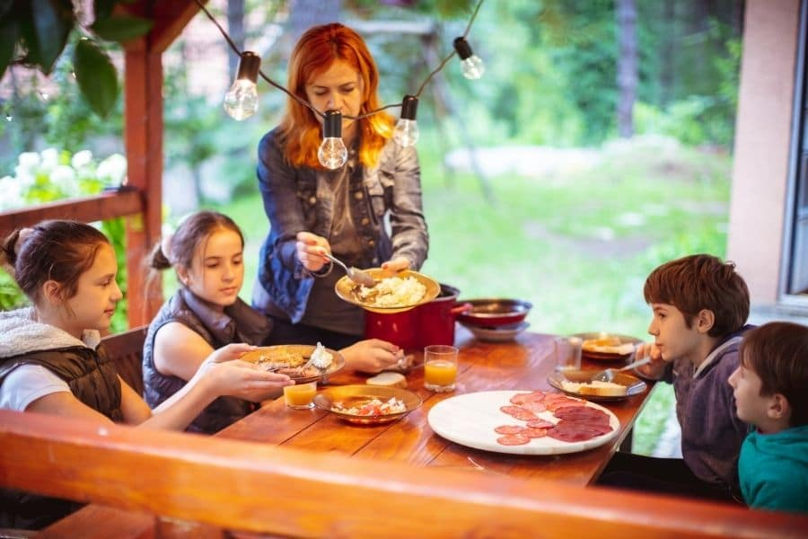 a mother serving her children food as they eat food on a porch