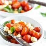 two white bowls filled with caprese salad and a fork resting on top