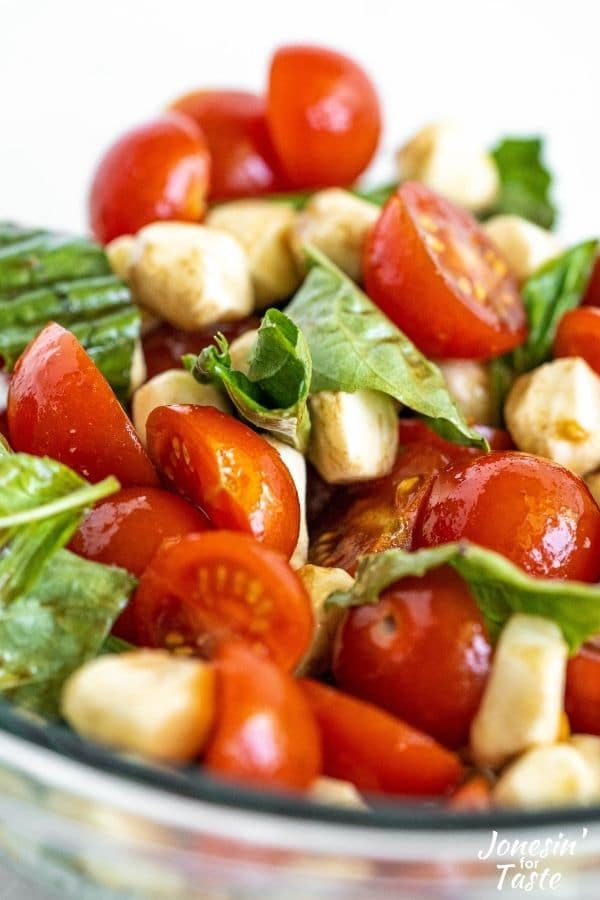 a close up shot of mozzarella, tomatoes, and basil coated in a balsamic vinaigrette